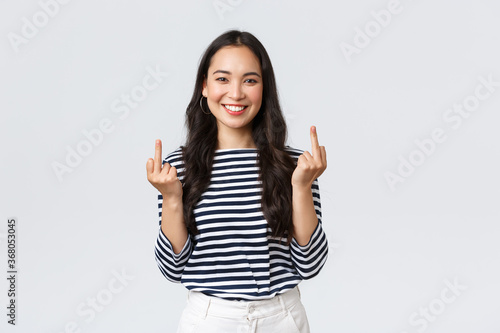 Lifestyle, beauty and fashion, people emotions concept. Unbothered and careless young happy smiling woman dont give a damn, showing middle fingers and feeling good, white background