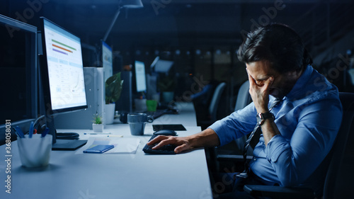 In the Office at Night Overworked Tired Office Worker Uses Desktop Computer and Covers His Face With his Hand. Tired Exhausted Businessman Finishing Important Project