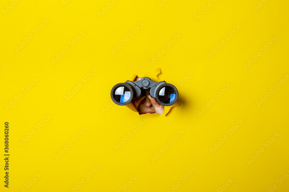 Fototapeta Female hand holds black binoculars on a yellow background. Journey, find and search concept