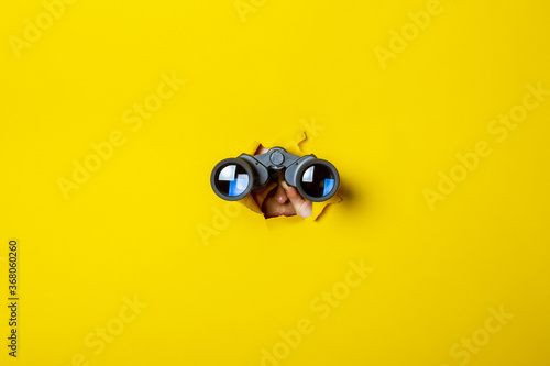 Fotografie, Tablou Female hand holds black binoculars on a yellow background