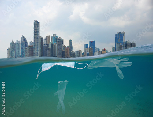 Fototapeta Plastic waste pollution in the ocean, face mask with gloves underwater and city buildings with cloudy sky, coronavirus COVID-19 pandemic, split view over and under water surface obraz