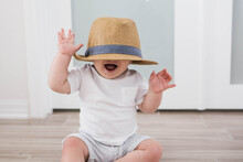 Baby Playing With A Straw Hat