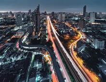 Aerial View Of Trident Road At Sathorn, Taksin Bridge And Illuminated Traffic At Dawn In Bangkok