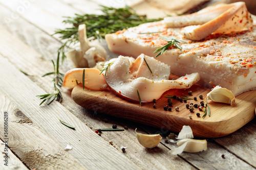 Canvastavla Lard with spices and herbs on a old wooden table.
