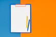 Blank clipboard mockup and two pens on blue-orange color background. Top view, copy space. Back to school, deadline, morning concept.