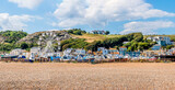 A panorama view of the old town beach in Hastings, Sussex with the west cliff backdrop in summer