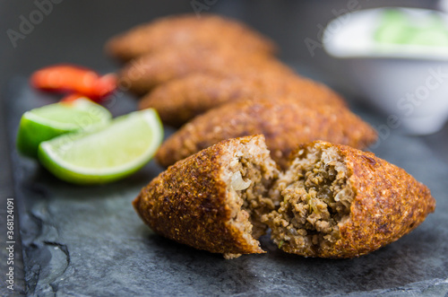 Obraz Delicious Lebanese  food, kibbeh (kibe) on black slate stone and granite background. - fototapety do salonu