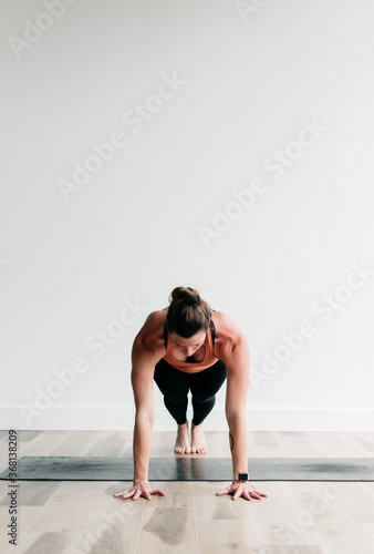 Canvas Print Woman holding plank pose in yoga studio portrait
