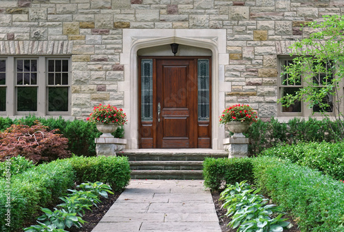 Fotomural Stone faced house with shrubbery and elegant wooden front door with sidelights