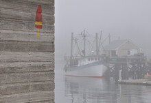 Foggy Summer Morning At Picturesque Fishing Village Of Port Clyde In Mid-coast Maine.  Fishing Trawler Docked In Quiet Harbor Enshrouded In Fog.