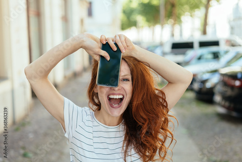 Laughing young woman holding up her mobile Tapéta, Fotótapéta