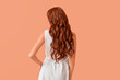 Beautiful young redhead woman on color background, back view