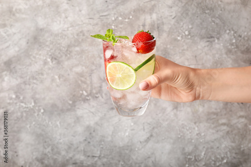 Obraz Hand with glass of fresh strawberry lemonade on grey background - fototapety do salonu