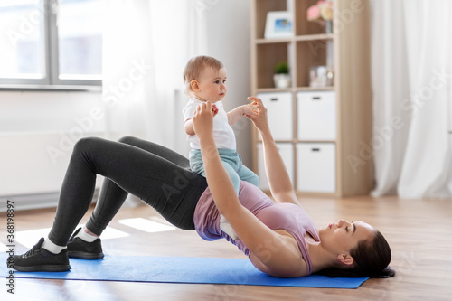 Fototapeta family, sport and motherhood concept - mother with little baby exercising at home obraz