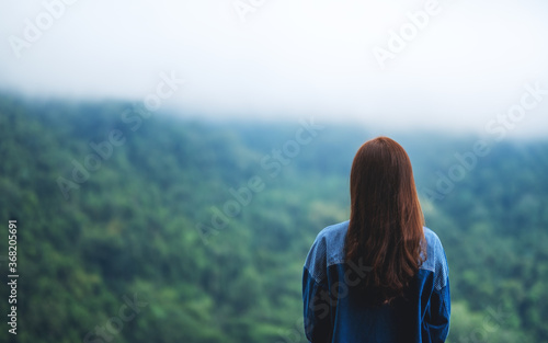 Rear view image of a female traveler looking at a beautiful green mountain on fo Fotobehang