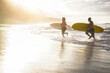 canvas print picture - Father and son running on the beach at sunset for surf training - Family people having fun doing extreme sport - Joyful elderly and healthy lifestyle concept - Focus on left guy face