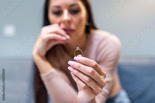 Canvas Print Closeup of a single sad wife after divorce lamenting holding the wedding ring in