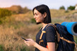 canvas print picture Young mountaineer girl with a big backpack  sending a message or email with the mobile at outdoors