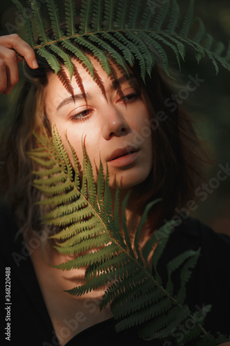 dark-haired girl with  fern in her hands near face and sun glare on her face Fototapeta