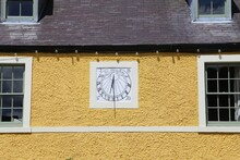 An  Ancient Sundial On A Rough Cast Yellow Wall Of A House.