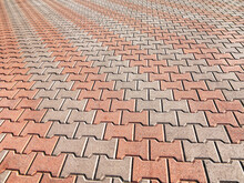 Decorative Colorful Sidewalk Pavement. Tiled Floor With Grey Tiles Crossed By A Diagonal Double Stripe Of Red Tiles Viewed At A Low Angle, Full Frame Background Pattern