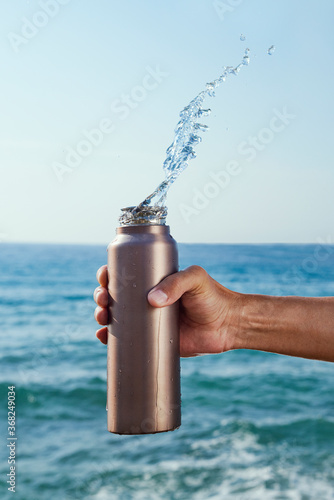 pouring water out of an aluminum reusable bottle - 368249034
