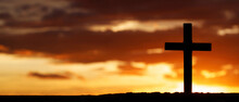 Silhouette Cross Against The Sky At Sunset. Dramatic Nature Background. Crucifixion Of Jesus Christ. Religion Concept.