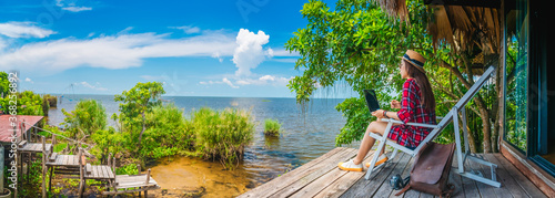 Panorama traveler woman using laptop on chair in front of nature scenic landscap Canvas