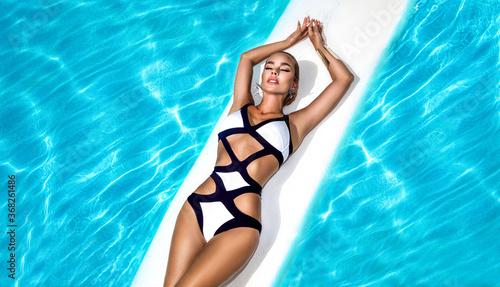 Fototapeta Elegant sexy woman in the black and white bikini on the sun-tanned slim and shapely body is posing near the swimming pool - Image obraz na płótnie