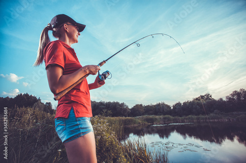 Cute woman is fishing with rod on lake Canvas Print