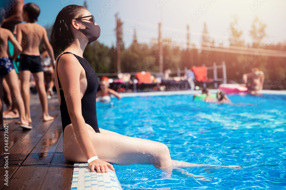 Fototapeta Woman in black protective mask from coronavirus bathes in hotel pool, summer epidemic vacation. Social distance concept