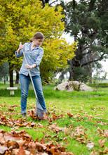 Girls Raking Fallen Autumn Leaves In Garden