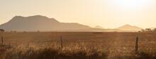 Golden Light Over Summer Fields To Mountain Range