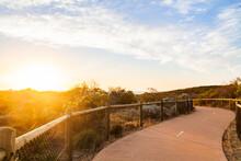 Golden Sunlight Shining Over Coastal Walking Path