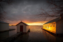 Old Boat Sheds On Lake At Sunset