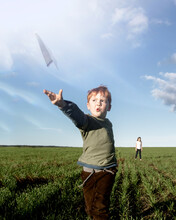Young Boy Flying A Paper Aeroplane In A Green Farm Paddock