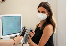 Young Shop Assistant With A Face Mask Using A Credit Card Terminal To Pay With The Contacless Smartphone. Card Terminal Protected For Better Hygiene With A Plastic Film. Visa, Mastercard, American