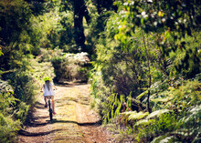 Girl Riding A Bike Down A Dirt Road Surrounded By Dense Bush