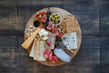 Top Down View Of Cheese Board On Wooden Table With Cheese, Crackers, Olives And Fruit
