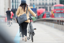 Businesswoman Walking Bicycle Along City Bridge, London, UK