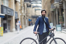 Portrait Confident Businessman With Bicycle In City Street
