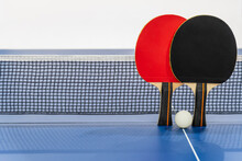 Black And Red Table Tennis Racket And A White Ball On The Blue Ping Pong Table With A Net, Two Table Tennis Paddle Is A Sports Competition Equipment Indoor Activity And Exercise For Background Concept