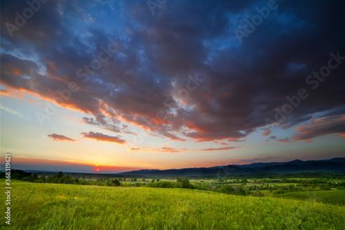 Fotografija Dramatic sunset over green field