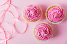 A Beautiful Cupcakes With Bright Pink Cream And A Little Silver Decoration On A Pink Background. Pink Ribbon For Decor In The Foreground Lies In Waves. Festive Background With Free Space.