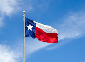 Texas State flag on the pole waving in the wing against blue sky and white clouds