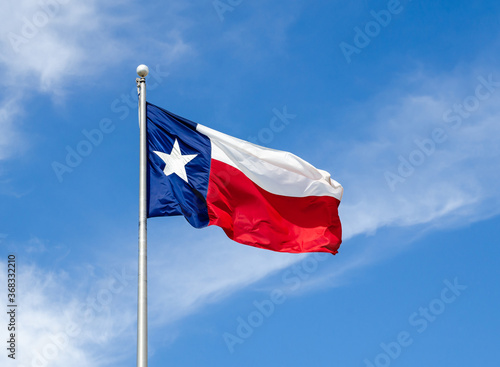 Texas State flag on the pole waving in the wing against blue sky and white clouds - fototapety na wymiar