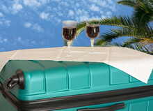Staycation With 2 Drinks Set On Upended Suitcase. Beyond Is The Blue Buttermilk Sky With Palm Tree, A Dream Of A Vacation That Is Not Happening.