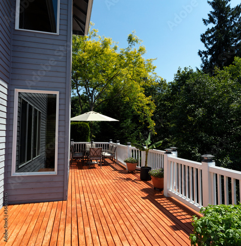 Fototapeta Outdoor home wooden deck during lovely summer day with seasonal garden obraz na płótnie