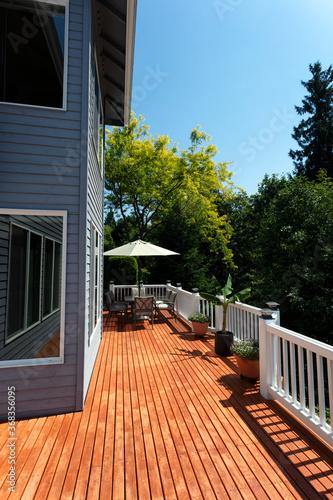 Fototapeta Outdoor home wooden cedar deck during lovely summer day with seasonal garden obraz na płótnie