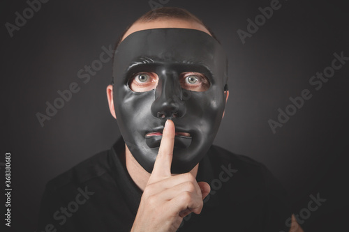 Fotografie, Obraz Man with a black mask making silence gesture. Fake, anonymous